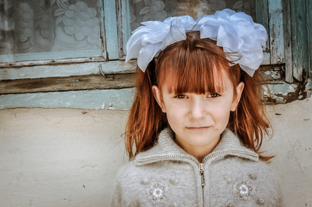 Karakol, Kyrgyzstan - circa September 2011: Small girl with red hair and white flower-like hair grips poses during her first day in school in Karakol, Kyrgyzstan. Documentary editorial.