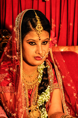 Dhaka, Bangladesh - circa July 2012: Bride with long black braid wears red glittering veil and beautiful dress during her wedding in Dhaka, Bangladesh. Documentary editorial.