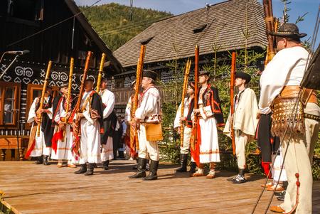 ÄŒičmany, Slovakia - circa September 2009: Men dressed in traditional folk costumes play fujaras at Shepherds pipe folk festival in ÄŒičmany. Documentary editorial. Redakční