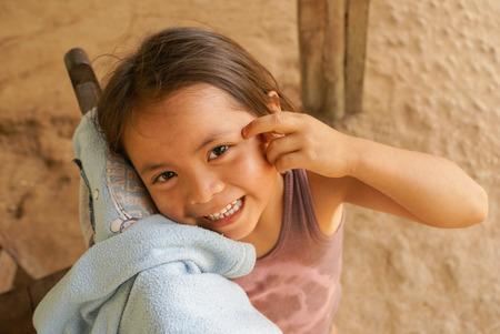 Villa Alcira, Bolivia -circa June 2009: Young smiling girl poses with hand on her face at Villa Alcira, Bolivia. Documentary editorial. Editorial
