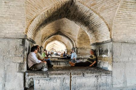 arcos de piedra: Esfahan, Iran - circa June 2011: Men sit and talk below stone arches in Esfahan, Iran. Documentary editorial.