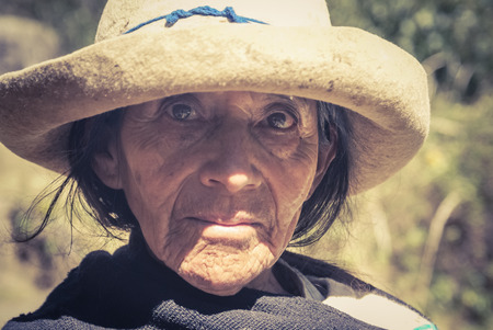 Parque Nacional Huascaran, Peru - circa July 2009: Old native woman with tanned and wrinkled face poses at Alpamayo in Peru. Documentary editorial.