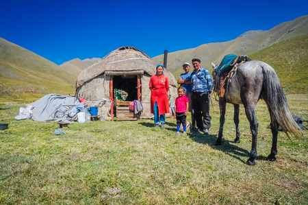 Ala Archa, Kyrgyzstan - circa September 2011: Smiling native family poses with their horse in front of their nomad tent on field in Ala Archa, Kyrgyzstan. Documentary editorial.