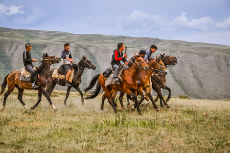 Karakol, Kyrgyzstan - circa July 2011: Native men sit on brown horses and play game, in which riders have to throw goat carcass into goal of opposing team. Documentary editorial.