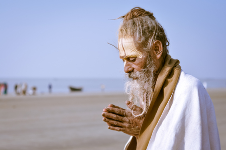 hinduist: Ganga Sagar, West Bengal - circa January 2012: Old native man in white coat and with yellow colour on forehead prays in Ganga Sagar, West Bengal. Documentary editorial.