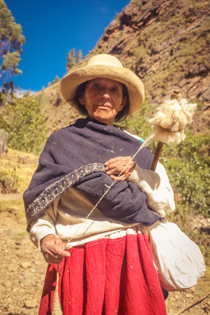 Parque Nacional Huascaran, Peru - circa July 2009: Old native woman dressed in traditional clothes and white hat poses at Parque Nacional Huascaran, Alpamayo in Peru. Documentary editorial.