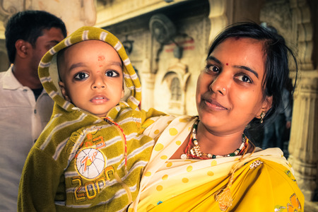 Bikaner, Rajasthan - circa December 2011: Native woman in yellow dress and with bindi on forehead poses with son in her arms during wedding in Bikaner, Rajasthan. Documentary editorial.