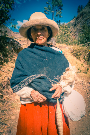 Parque Nacional Huascaran, Peru - circa July 2009: Old native woman in traditional red skirt and white hat poses at Alpamayo in Peru. Documentary editorial.