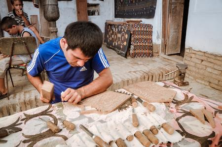 uzbekistan: Khiva, Uzbekistan - circa July 2011: Skillful man engraves ornaments into wood in Khiva, Uzbekistan. Documentary editorial.