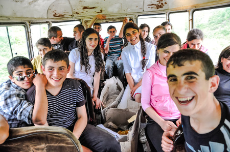 Stepanakert, Nagorno-Karabakh - circa May 2011: Young smiling girls and boys travel by bus. Documentary editorial.