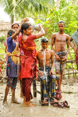 Paigacha, Bangladesh - circa July 2012: Young girls stand barefoot in mud and pour water from jars on head of halfnaked sitting boy in Paigacha, Bangladesh. Documentary editorial. Editorial