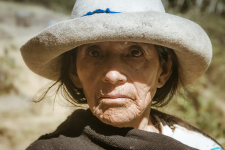 Parque Nacional Huascaran, Peru - circa July 2009: Old native woman with tanned wrinkled face and white hat at Parque Nacional Huascaran, Alpamayo in Peru. Documentary editorial. Editorial