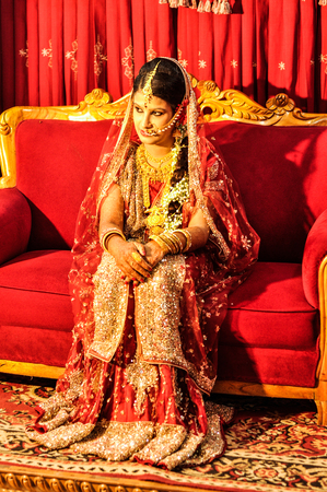 Dhaka, Bangladesh - circa July 2012: Young bride with long black hair dressed in beautiful red and gold glittering dress sits on red couch in Dhaka, Bangladesh. Documentary editorial.