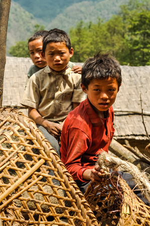 Kanchenjunga Trek, Nepal - circa May 2012: Photo of three young boys sitting next to baskets in Kanchenjunga Trek, Nepal. Documentary editorial.
