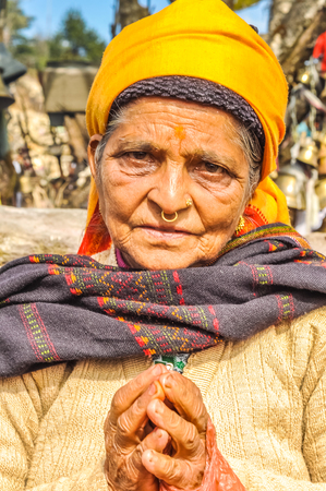 Pathivara Devi, Nepal - circa May 2012: Old woman with yellow headcloth and piercing in her nose with her hands in prayer in Pathivara Devi, Nepal. Documentary editorial.