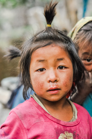 ponytails: Dolpo, Nepal - circa May 2012: Young brown-eyed girl with brown ponytails dressed in pink has golden piercing in her nose in Dolpo, Nepal. Documentary editorial.
