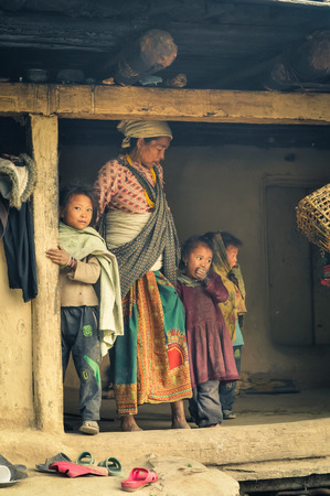 headcloth: Dolpo, Nepal - circa May 2012: Native woman with white headcloth looks down and poses with her three young children in their wooden house in Dolpo, Nepal. Documentary editorial. Editorial