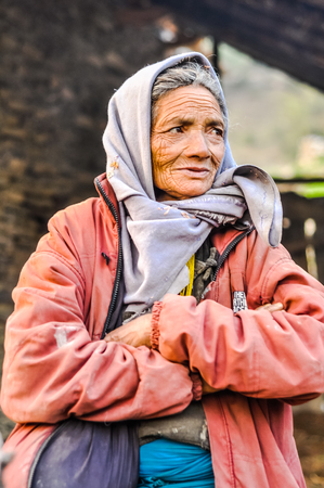 headcloth: Dolpo, Nepal - circa May 2012: Old woman with wrinkles and with grey headcloth wears pink jacket and looks to right in Dolpo, Nepal. Documentary editorial.