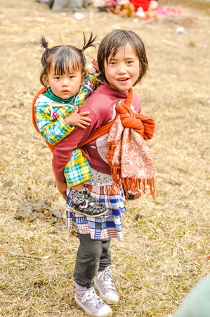 arunachal pradesh: Dorjeling, Arunachal Pradesh - circa March 2012: Young girl carries her younger sister on her back in scarf and they look to photocamera in Dorjeling, Arunachal Pradesh. Documentary editorial.