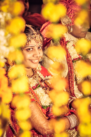 Bikaner, Rajasthan - circa December 2011: Young smiling bride sits behind yellow decorations during her wedding in Bikaner, Rajasthan. Documentary editorial.