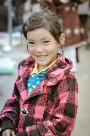 Bohdgaya, Bihar - circa January 2012: Small girl in pink and black coat in Bohdgaya, Bihar. Documentary editorial. Editorial