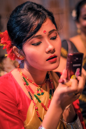 Guwahati, Assam - circa April 2012: Beautiful girl in traditional dress and with red dot on her forehead looks down to her mobile phone at Bihu festival in Guwahati, Assam. Documentary editorial.