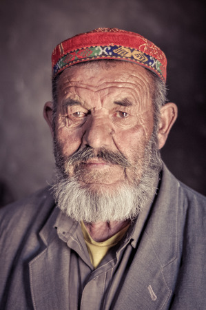 Karakul, Tajikistan - circa September 2011: Old man with grey beard and wrinkled face in Karakul, Tajikistan. He wears traditional colourful cap on his head. Documentary editorial.
