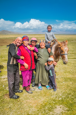 Son Kol, Kyrgyzstan - circa September 2011: Smiling native family poses in Son Kol, Kyrgyzstan. In the backgroud with young boy on horse. Documentary editorial. Editorial
