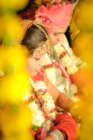 Bikaner, Rajasthan - circa December 2011: Young groom and bride have their heads down and sit behind yellow decorations during their wedding in Bikaner, Rajasthan. Documentary editorial. Editorial