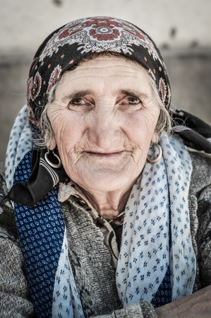 headcloth: Khorog, Tajikistan - circa September 2011: Older woman with humble sight and headcloth on her head smiles nicely to photocamera in Khorog, Tajikistan. Documentary editorial.
