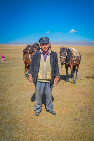 kyrgyzstan: Son Kol, Kyrgyzstan - circa September 2011: Older man with cap poses in field near his nomad tent in Son Kol, Kyrgyzstan. In the background with two brown horses. Documentary editorial.