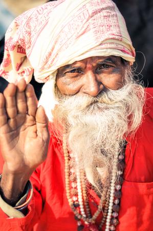hinduist: Ganga Sagar, West Bengal - circa January 2012: Old native man in red clothes with grey beard wears headcloth and waves to photocamera in Ganga Sagar, West Bengal. Documentary editorial.