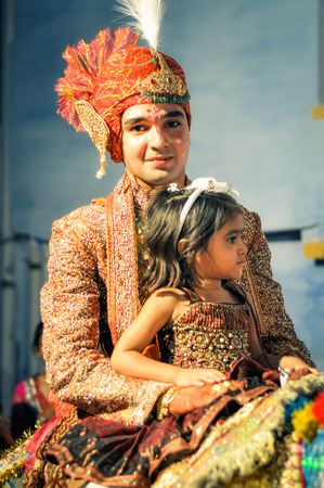 Bikaner, Rajasthan - circa December 2011: Groom dressed in beautiful clothes and turban poses with small girl on his knees during wedding ceremony in Bikaner, Rajasthan. Documentary editorial. Editorial