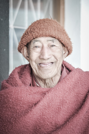 arunachal pradesh: Tawang, Arunachal Pradesh - circa February 2012: Older man in red with orange cap on his head smiles and looks happily to photocamera in Tawang, Arunachal Pradesh. Documentary editorial.