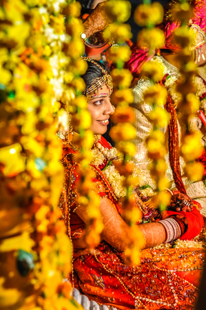 Bikaner, Rajasthan - circa December 2011: Photo of smiling bride behind yellow decorations during wedding ceremony in Bikaner, Rajasthan. Documentary editorial. Editorial