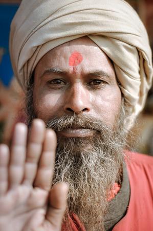 hinduist: Ganga Sagar, West Bengal - circa January 2012: Man with long grey beard and red dot on forehead wears turban and holds his hand towards photocamera in Ganga Sagar, West Bengal. Documentary editorial. Editorial