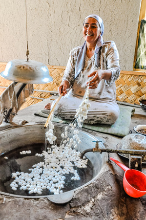 Margilan, Uzbekistan - circa July 2011: Smiling woman sits on ground and adds silk worm cocoons to vat with water in silk factory in Margilan. Documentary editorial.