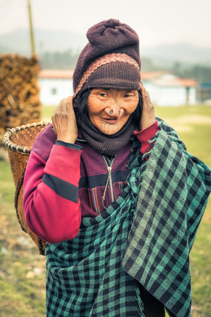 Ziro, Arunachal Pradesh - circa March 2012: Apatani woman with typical tattoo and large nose plugs carries wicker basket on her back using her head in Ziro, Arunachal Pradesh. Documentary editorial.