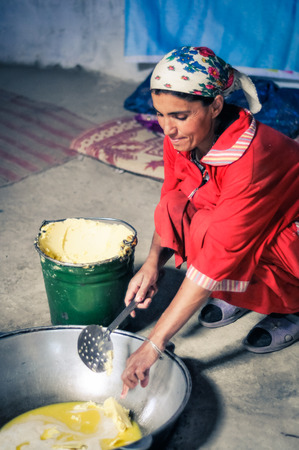 adds: Wakhan valley, Tajikistan - circa October 2011: Woman in red clothes kneels and adds butter to large pot in Wakhan valley, Tajikistan. Documentary editorial. Editorial