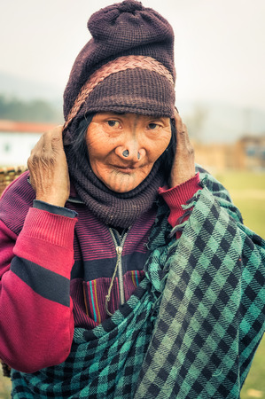 Ziro, Arunachal Pradesh - circa March 2012: Apatani woman with typical tattoo and large nose plugs carries wicker basket in Ziro, Arunachal Pradesh. Documentary editorial.