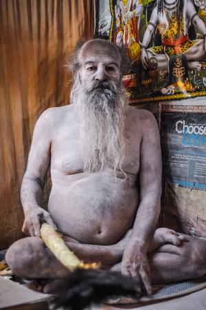 hinduist: Ganga Sagar, West Bengal - circa January 2012: Man covered with white powder sits on ground in Ganga Sagar, West Bengal. Documentary editorial.
