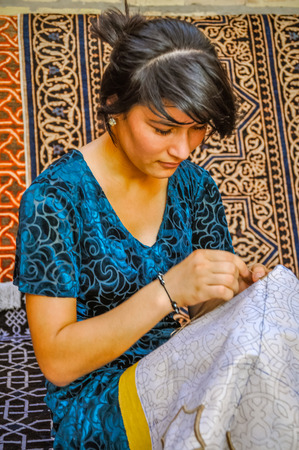 Khiva, Uzbekistan - circa July 2011: Young woman embroiders table clothing at marketplace in Khiva, Uzbekistan. Documentary editorial. Editorial