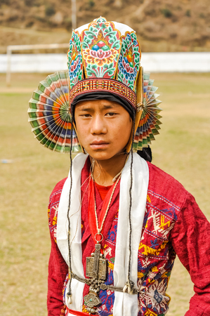 arunachal pradesh: Dirang, Arunachal Pradesh - circa February 2012: Young boy with traditional colourful hat on his head looks sadly to photocamera in Dirang, Arunachal Pradesh. Documentary editorial. Editorial