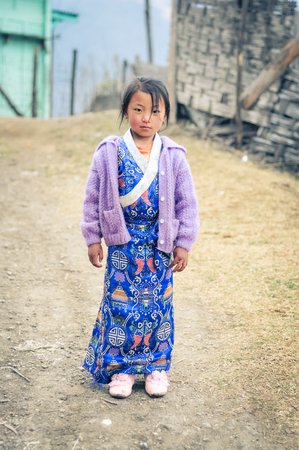 arunachal pradesh: Khinmey Gompa and Ugyenling Temple, Arunachal Pradesh - circa February 2012: Young native girl poses in blue and white ornamented dress in Khinmey Gompa, Arunachal Pradesh. Documentary editorial.
