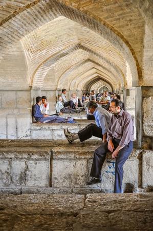 arcos de piedra: Esfahan, Iran - circa June 2011: Men sit below stone arches in Irans third largest city, Esfahan. Documentary editorial.