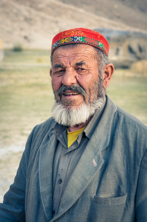 Khorog, Tajikistan - circa September 2011: Old man with tanned and wrinkled face in Khorog, Tajikistan. He wears grey suit and colourful cap. Documentary editorial.
