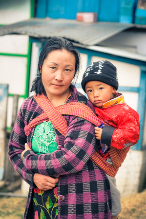 arunachal pradesh: Khinmey Gompa and Ugyenling Temple, Arunachal Pradesh - circa February 2012: Woman with black hair carries her young son on her back in Khinmey Gompa, Arunachal Pradesh. Documentary editorial.