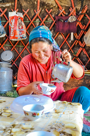 headcloth: Ala Archa, Kyrgyzstan - circa September 2011: Smiling native woman dressed in red t-shirt and with headcloth on her head pours tea into cup in Ala Archa, Kyrgyzstan. Documentary editorial.