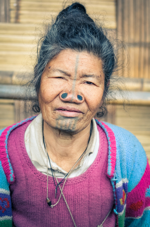 Ziro, Arunachal Pradesh - circa March 2012: Apatani woman with typical tattoo and large nose plugs in Ziro, Arunachal Pradesh. Documentary editorial.