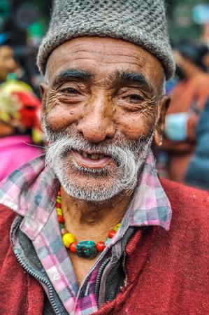 Bohdgaya, Bihar - circa January 2012: Smiling man with grey beard on tanned face and cap on his head at school in Bohdgaya, Bihar. Documentary editorial.